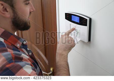 Man Entering Code On Home Security System Near Door, Closeup
