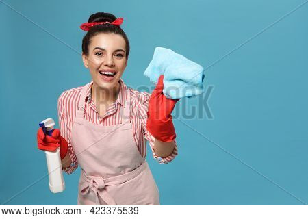 Young Housewife With Detergent And Rug On Light Blue Background, Space For Text