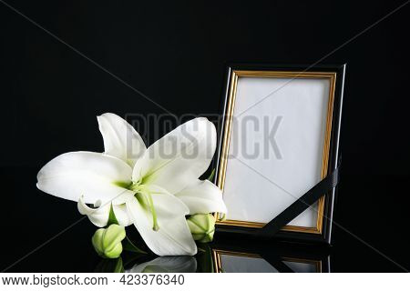 Funeral Photo Frame With Ribbon And White Lily On Black Table Against Dark Background. Space For Des