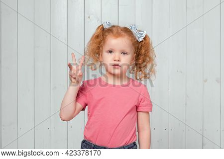Portrait Of Cute Ginger Little Girl 4-6 Years Old Showing Three Fingers. Studio Shot, Light Wooden B