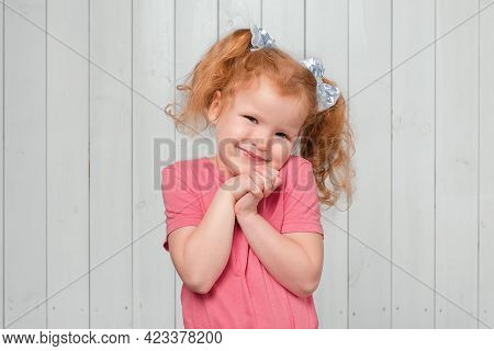 Portrait Of Cute Redhead Little Girl, Holding Hands Near Face And Daydreaming, Gazing At Something L
