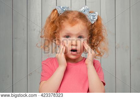 Close Up Of Scared Timid Ginger Little Girl In Casual Pink T Shirt, Looking Frightened And Anxious,