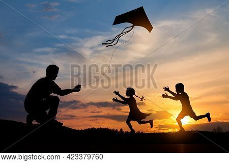 Happy Family On The Field. Father And Kids Playing With A Kite While Running On Meadow On The Backgr