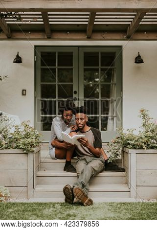 Cute black couple reading a book together in a garden