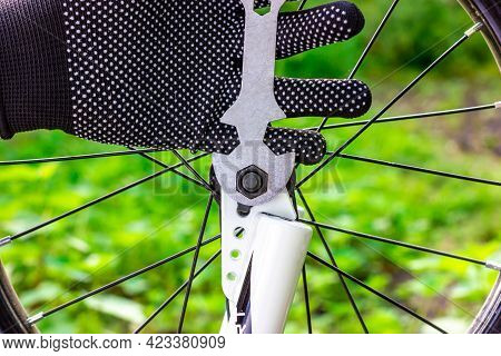 Bicycle Key In Hand. Tightening The Nut On The Bicycle Wheel. Installing A Bicycle Wheel. Bicycle Re