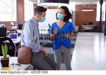 Diverse male and female colleague in face masks looking at tablet and discussing standing in office. working in business at a modern office during coronavirus covid 19 pandemic. .