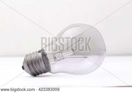 Vintage Retro Filament Lamp Light Bulb With Broken Wire Laying On White Table
