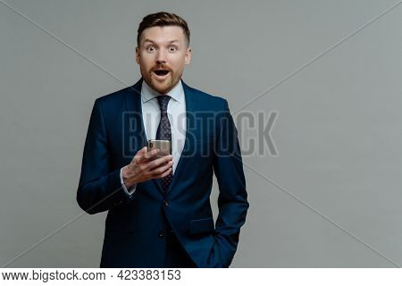 Surprised Businessman In Suit Holding Smartphone And Looking At Camera With Shocked Face Expression,
