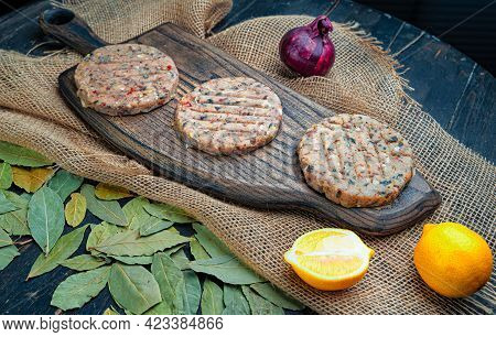 Uncooked Sea Bass Fish Cutletson A Wooden Board.