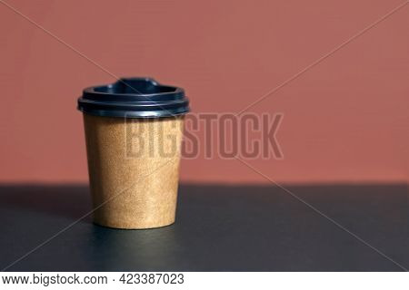 Disposable Coffee Cup For Cafe On A Bar Table. Brown Cardboard Mockup Of Eco Coffee Cup With Place F