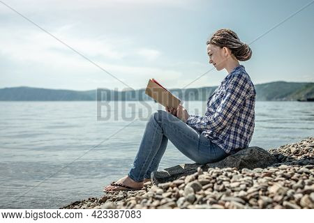 Young Woman Is Sitting On The Stony Coast Of A Large Pond, Reading And Enjoying The Solitude And Nat