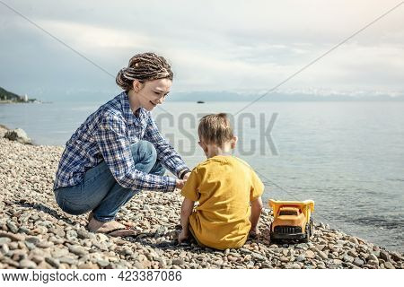 Happy Mother And Little Son On The Shore Of A Large Pond Are Playing Together And Collecting Stones.