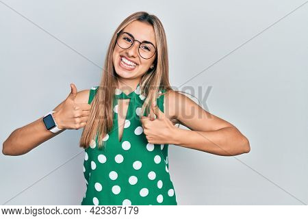 Beautiful hispanic woman wearing elegant shirt and glasses success sign doing positive gesture with hand, thumbs up smiling and happy. cheerful expression and winner gesture.