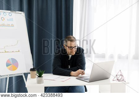 Attractive Guy In Casual Wear At Home, He Is Typing On The Keyboard And Watching On The Screen. Web