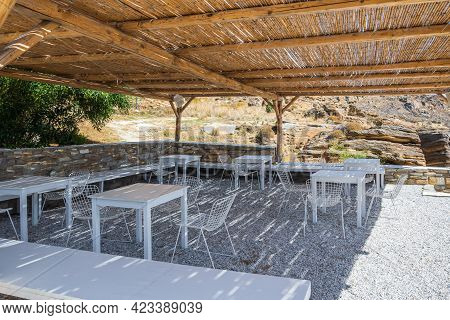 Paros, Greece - September 29, 2020: Tables And Chairs At The Local Tavern On The Monastiri Beach. Pa