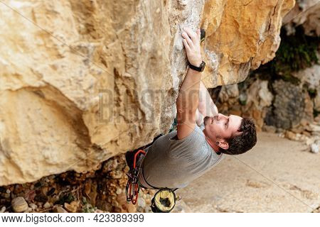 Climber Overcoming An Obstacle In The Rock. Man Climbing Mountain. Outdoor Sports And Healthy Lifest