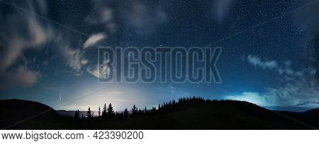 Magnificent Panoramic View Of Night Starry Sky Over Coniferous Wood In Mountains. Fantastic Landscap