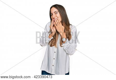Young beautiful woman wearing casual clothes laughing and embarrassed giggle covering mouth with hands, gossip and scandal concept