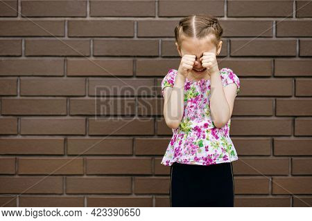A Little Girl With A Beautiful Hairstyle Is Very Upset And Cries, Wiping Her Eyes With Her Hands. Pr