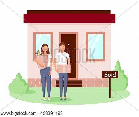 A Happy Young Family Bought A New Home. A Man And A Woman Are Standing With Boxes Near Their House.