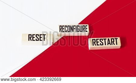 Reset. Reconfigure. Restart Text On Wood Blocks And Red And White Background