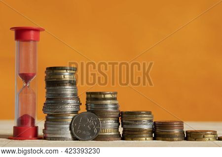 The Red Hourglass And The Stacks Of Coins Stand In A Single Row In Descending Order. A Ruble Coin Lo