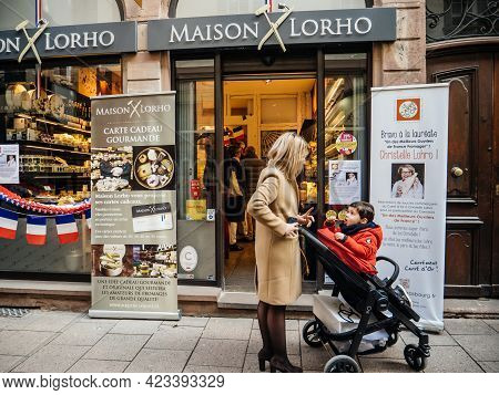 Strasbourg, France - Circa 2020: Mother With Child Walking In Front Of Maison Lorho With Announcemen
