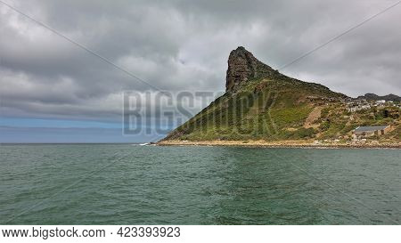 Cape In The Atlantic Ocean. A Picturesque Mountain With Bizarre Outlines And A Sharp Peak Against Th