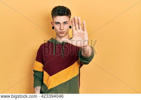 Young caucasian boy with ears dilation wearing casual sweatshirt doing stop sing with palm of the hand. warning expression with negative and serious gesture on the face.
