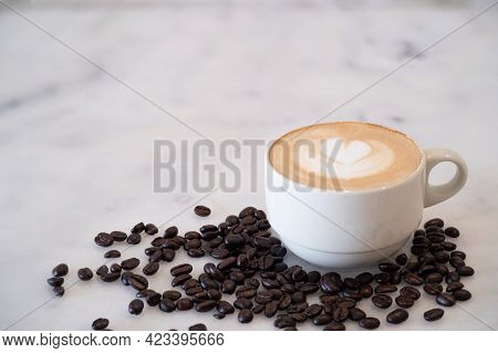 Close-up Of Hot Coffee Latte With Latte Art Milk Foam In Cup Or Mug On Desk With Coffee Beans In Cof