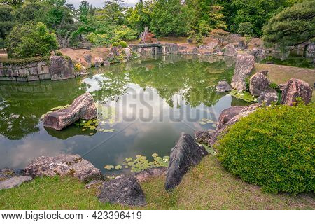 Old, Traditional Japanese Garden With Precisely Cut Trees, Small Pond And Stone Bridges. Trees Refle