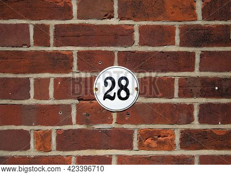 Number 28 On Old Red Brick Wall. Black Number 28 On White Round House Plate. Antique Uk House Number
