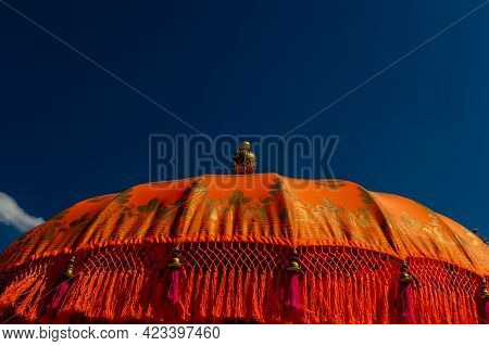 A Close-up Of Bright Orange And Gold Indian Parasol With Pink Tassels Against A Blue Sky On A Sunny