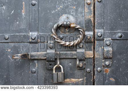 Padlock Is Hinged On Latch Of Old Door.