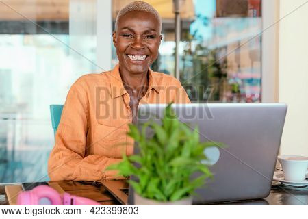 Happy African Woman Working Online Using Laptop In Bar Restaurant - Digital Nomad And Freelance Life
