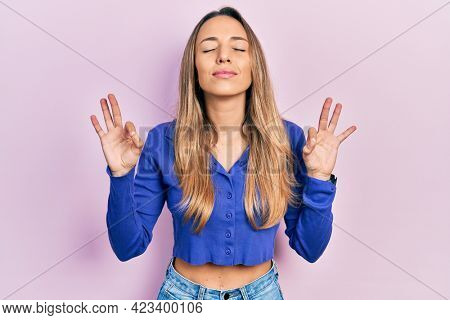 Beautiful hispanic woman wearing casual blue shirt relaxed and smiling with eyes closed doing meditation gesture with fingers. yoga concept.