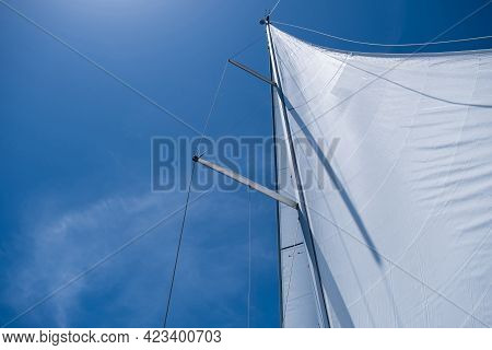Yacht Sails On Clear Blue Sky Background. Sailing With The Wind At Open Sea Ocean, Summer Holidays