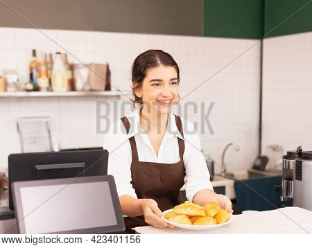 Beautiful Caucasian Barista Woman Taking Plate With Bread From Coffee Bar For Customer.