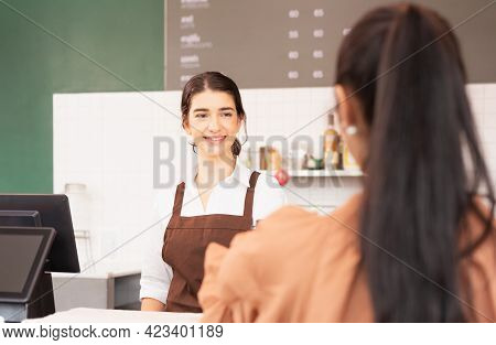 Beautiful Caucasian Barista Woman Stand To Welcome Customer And Receiving Order From Customer At Cof