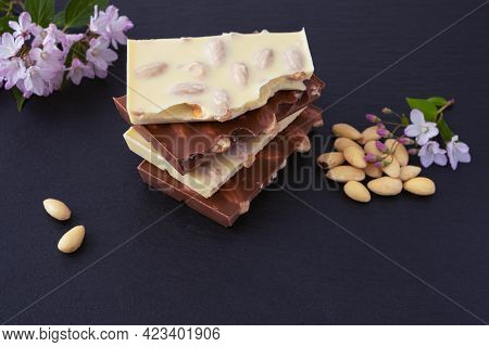 Bars Of Milk And White Chocolate With Almond Nuts And A Bunch Of Almonds, A Sprig With Flowers, On A