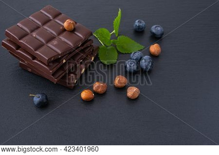 Chocolate Bars With Hazelnuts, Next To Blueberries And Hazelnut Itself, On A Black Background