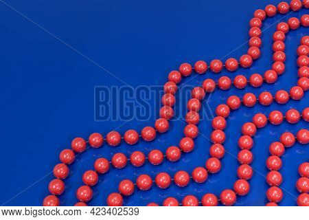 A Background Of Strands Of Red Plastic Beads On A Blue Surface. The Beads Are Arranged In A Wave Dia