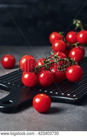 Fresh Red Cherry Tomatoes On The Vine. Dark Background.