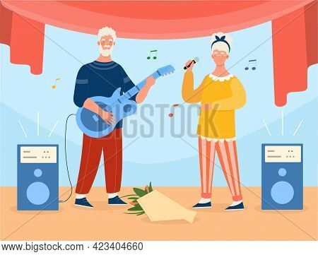 Grey Elderly Couple Is Playing Guitar And Singing On Stage. Concept Of Active Elderly People Full Of