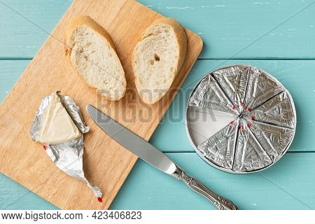Making Sandwich With Processed Cream Cheese And Sliced Bread On A Cutting Board Over Blue Wooden Tab
