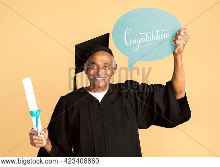 Proud senior man in a graduation gown holding a congratulations speech bubble mockup