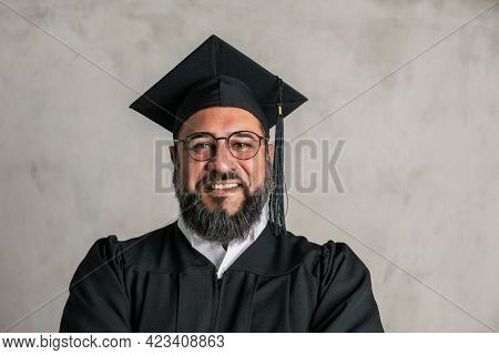 Proud senior man in a graduation gown