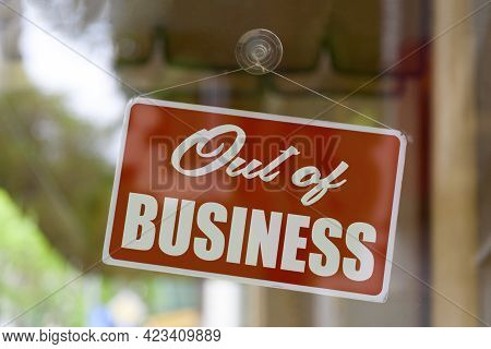 Close-up On A Red Sign In The Window Of A Shop Displaying The Message: Out Of Business.