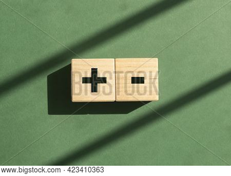 Plus And Minus Signs On Dices On Green Background With Day Light. Concept Of Positive And Negative,