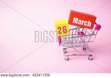 March 26th. Day 26 Of Month, Calendar Date. Close Up Toy Metal Shopping Cart With Red And Yellow Box